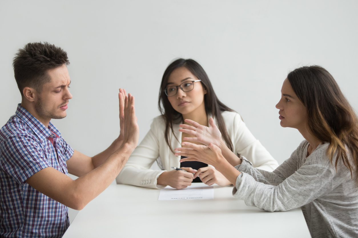 Unhappy married couple getting divorced arguing fighting in lawyers office