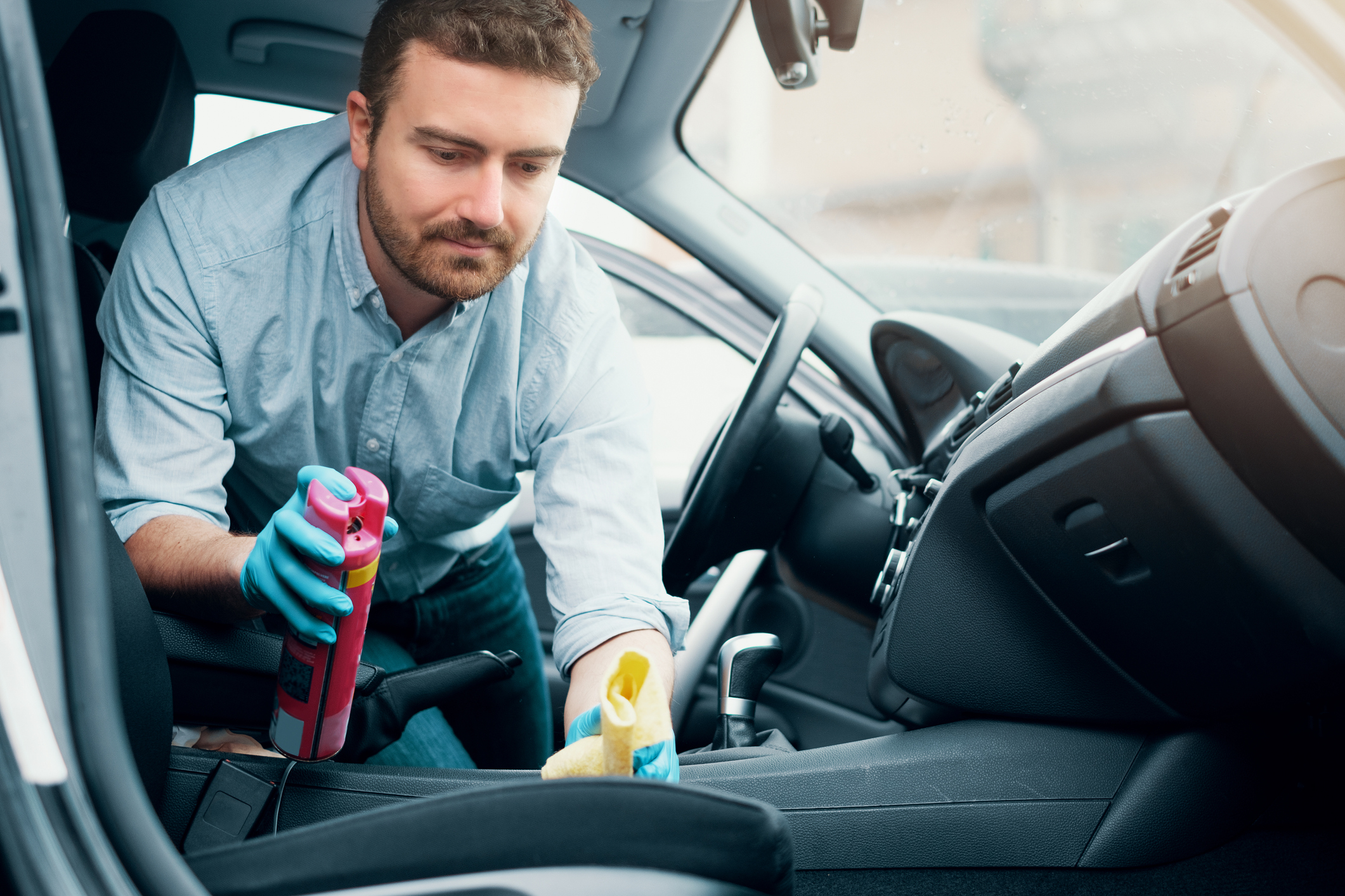 Man cleaning his car interiors and dashboard from dust